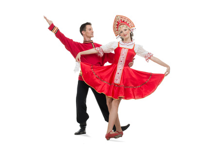 Couple of dancers in russian traditional costumes, girl in red sarafan and kokoshnik, boy in black trousers and red shirt   Studio shot isolated on white  Standard-Bild