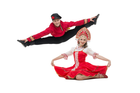 Couple of dancers in russian traditional costumes, girl in red sarafan and kokoshnik, boy in black trousers and red shirt   Man makes a jump  Studio shot isolated on white