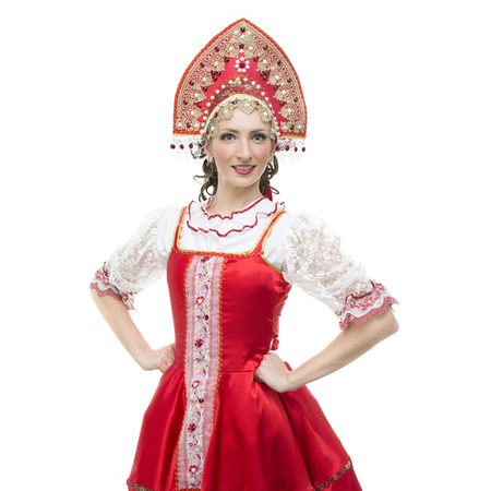 Smile young woman hands on hips portrait  in russian traditional costume --  red sarafan and kokoshnik  Studio shot isolated on white  Stock Photo