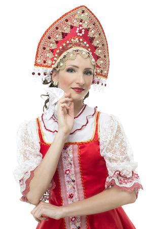 kokoshnik: Smile coquettish young woman portrait  in russian traditional costume --  red sarafan and kokoshnik  Studio shot isolated on white