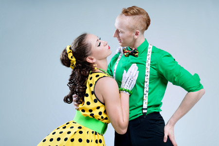 Portrait lovely funny dancer couple dressed in boogie-woogie rock n roll pin up style posing together in studio  Standard-Bild