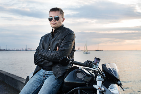 Handsome young man in leather jacket on motorcycle on sunset light on the sea embankment  Stock Photo
