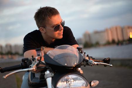 Romantic portrait handsome biker man in sunglasses sits on a bike on a sunset near lake and city Standard-Bild