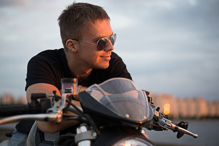 Romantic portrait handsome biker man in sunglasses sits on a bike on a sunset near lake and city photo