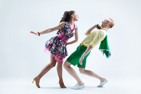 Funny dancer couple dressed in boogie-woogie rock n roll pin up style posing together in studio 스톡 콘텐츠