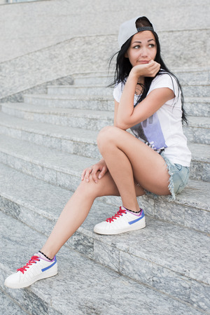 rueful: Young teenage girl with headphones,black long hair and jeans sitting on steps alone with rueful smile  Stock Photo
