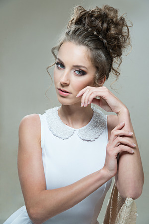 chignon: Glamour lady portrait in luxury dress. Beautiful model girl with perfect fashion makeup and hairstyle. Stock Photo