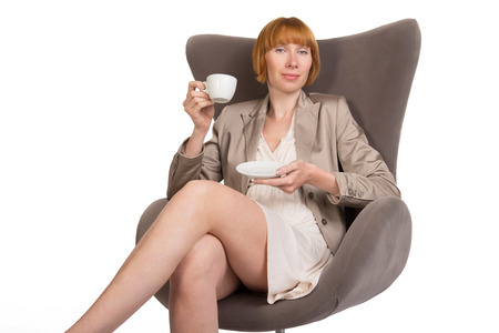 pretentious: Young lady in office style sitting on modern chair with a cup of coffee and pretentious smile