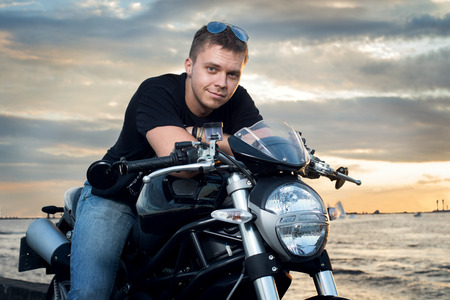 Friendly guy on a motorcycle smiling at the camera in the evening outdoor photo