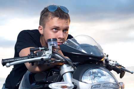 young man with a stubborn look leaned on the steering wheel of his bike photo