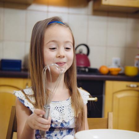 little dough: little  mothers helper. Small girl going to whisk dough for pancakes