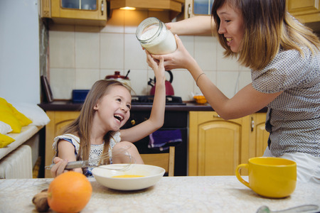 little  mothers helper. Small girl going to beat the dough for pancakes Stock Photo