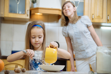 little dough: little  mothers helper. Small girl going to beat the dough for pancakes Stock Photo
