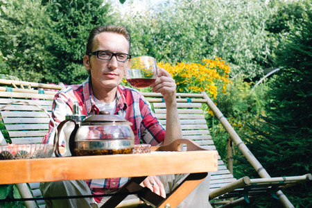 age 30 35 years: Man drinking tea in his own garden at summer day