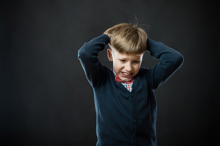 small boy hang his head in despair Standard-Bild