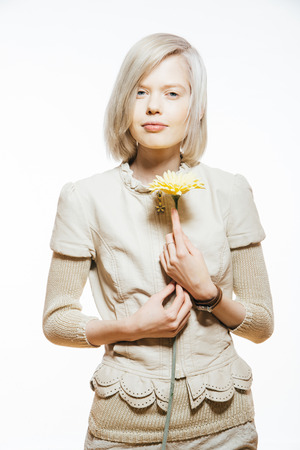 platinum hair: strange slim blonde girl with a yellow flower in her hand