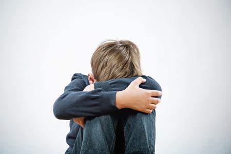 hugging knees: Upset boy sitting hug his knees, white