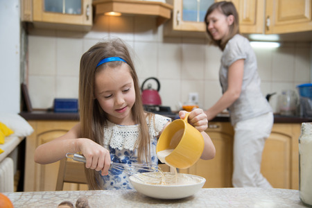 cook: little  mothers helper. Small girl going to beat the dough for pancakes. Mom teach daughter to cook Stock Photo