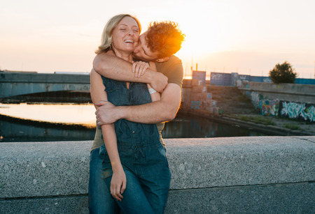 suburbia: happy hansome young couple embracing and laughing Stock Photo