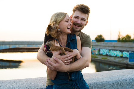 hansome: Happy hansome young couple with small dog embracing and laughing Stock Photo