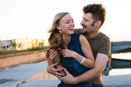 hansome: happy hansome young couple with small dog embracing and laughing