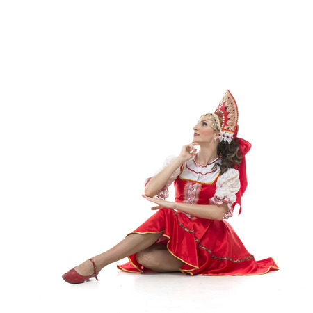 woman in national russian dress sitting on the floor and looking left top