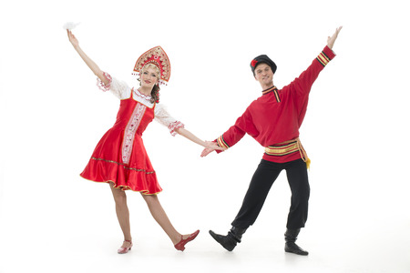 Dancing couple in russian national costumes hold hands