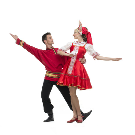 kokoshnik: Couple of dancers in russian traditional costumes girl in red sarafan and kokoshnik boy in black trousers and red shirt .embracing on dance pose Studio shot isolated on white. Stock Photo