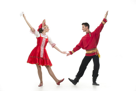 kokoshnik: Couple of dancers in russian traditional costumes girl in red sarafan and kokoshnik boy in black trousers and red shirt. Studio shot isolated on white.