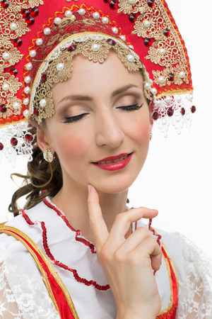 kokoshnik: Smile young woman hands on hips portrait in russian traditional costume red sarafan and kokoshnik. Studio shot isolated on white. Stock Photo