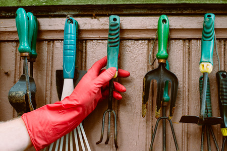 hand in red gloves takes old garden tools on the wall outdoor Standard-Bild
