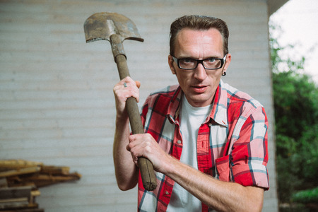 brandish: angry farmer in glasses attack with spade