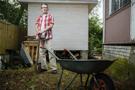 lean back: confident 30-40 years old farmer stand on his back yard and lean on the spade handle