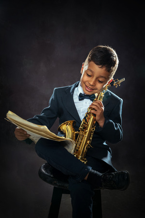 notation: six years old boy sit with saxophone and reading musical notation