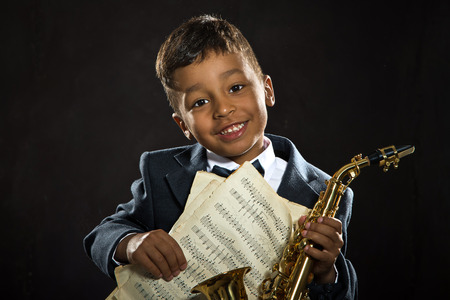 smile close up: six years old boy sit with saxophone and smile. close up portrait