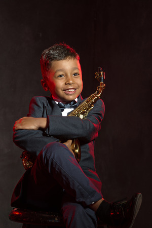 six years: six years old boy hug his saxophone  and smile Stock Photo