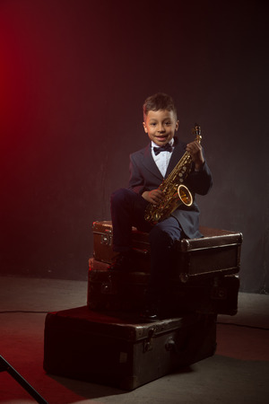 six years: six years old boy sit with saxophone on old siuitcases. instagrsm toned