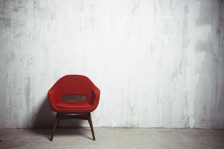 poltrona vermelha perto da parede cinza texturizada velha