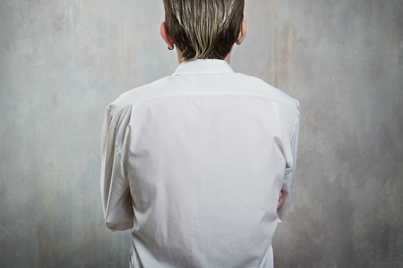 arms behind head: man back view in white shirt and arms cross