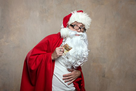 paid medicine: Sick old Santa in home clothes keeps a banknote and holds his stomach Paid medicine concept. Stock Photo