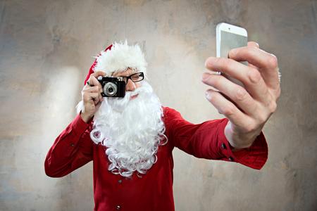 weihnachtsmann lustig: hipster Weihnachtsmann macht Selfy mit Retro-Kamera und Smartphone