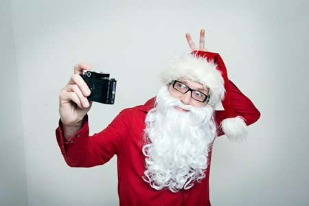 picture person: Hipster Santa fool around making selfie and show horns