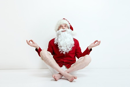 peace concept: santa in summer cloth meditate near white wall, concept of breaking rules and patterns, being yourself,