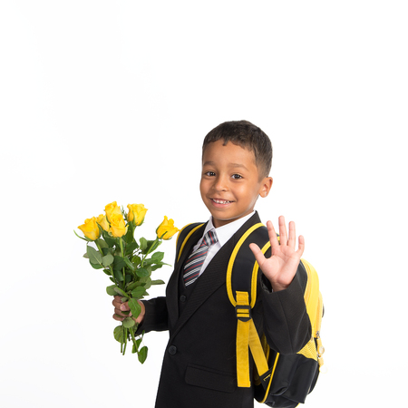 first day: Smiling black first-grader african boy in school uniform with the backpack and bouquet of roses at his first school day Stock Photo