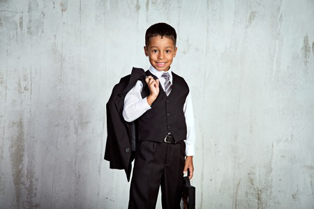 Smiling black first-grader african boy in school uniform with the backpack and bouquet of roses at his first school day Standard-Bild