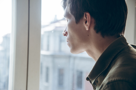 mournful: Young sad man looking out the window. close up.