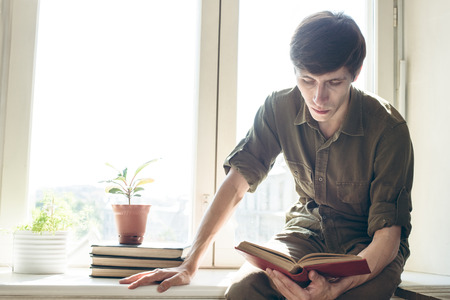 concentrated: concentrated serious young man read book before university exam