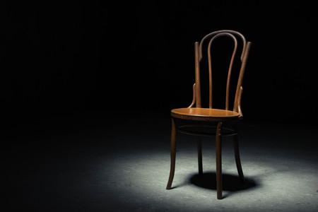 silla de madera: Silla sola en el punto de luz sobre fondo negro en el cuarto vacío Foto de archivo