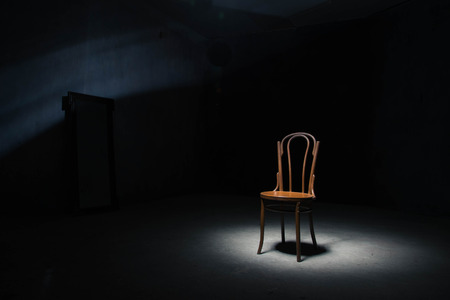 Lonely chair in the spot of light on black background at empty room Standard-Bild