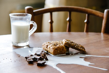 untidiness: Chocolate, bread and spilled milk on the table. Eco life concept.